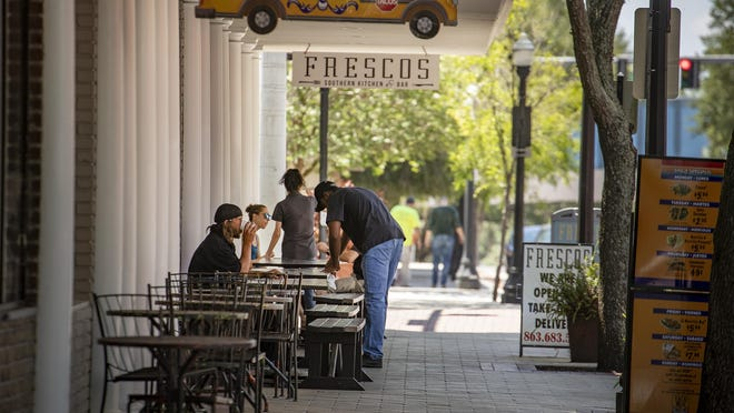Downtown lunch goers enjoy a meal outside Frescos in Lakeland in May. It was the first day under an order by Gov. Ron DeSantis that restaurants could open across the state, outside South Florida, and serve inside customers at 25% of capacity.