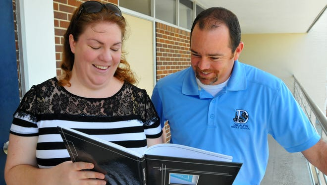 Anna Nagy, yearbook adviser at DeLaura Middle School, shows principal Bobby Pruett a page from the book. This year, DeLaura Middle won a national award for its yearbook design, in which each student was featured as a unique element from the periodic table.