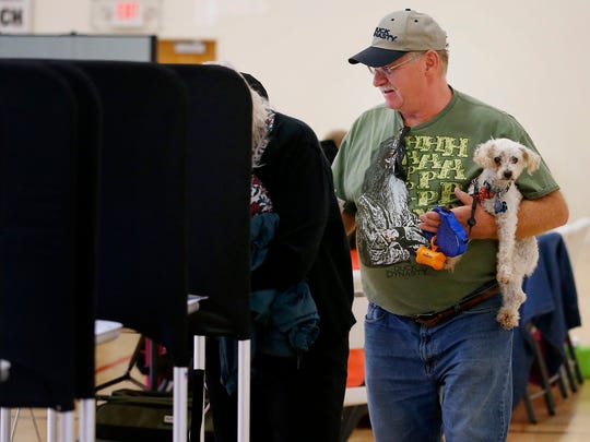 Bob Held, of Elmira, cradles Buddy, a miniature poodle, Tuesday while casting his vote in the mayoral and council race at New Beginnings Methodist Church in Elmira.