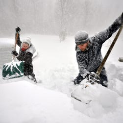 Tami Normile and Richard Brooks attempt to remove some of the five feet of snow from a roof top on Nov. 20, 2014 in the Lakeview neighborhood of Buffalo, New York.