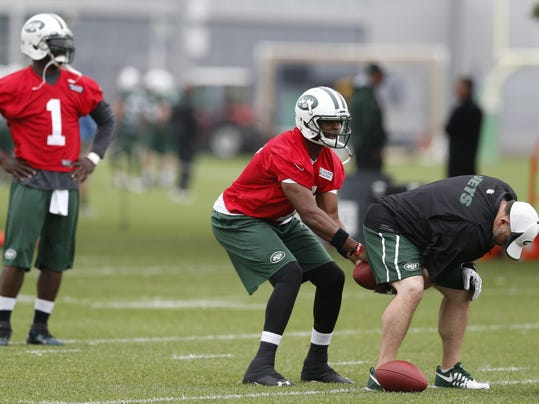 New York Jets quarterback Geno Smith, center, takes a snap while quarterback Michael Vick, left, looks on during an NFL football organized team activity, Wednesday, May 28, 2014, in Florham Park, N.J. (AP Photo/Julio Cortez)