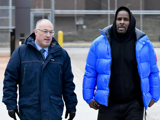 R. Kelly, right, leaves Cook County Jail with his defense