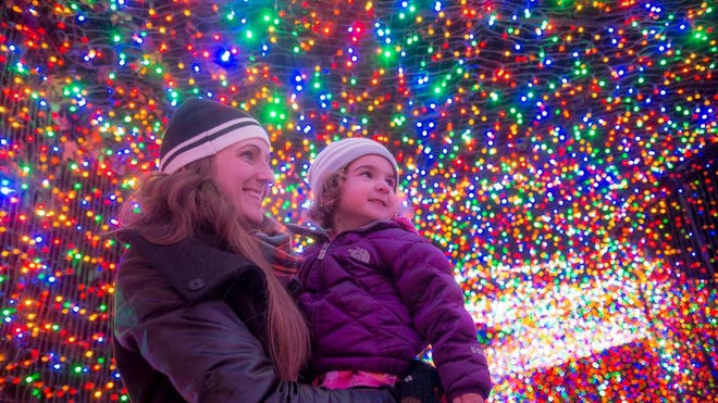 Sarah Johnson holds 2 year-old Samantha Johnson while in the light tunnel at Zoolights.