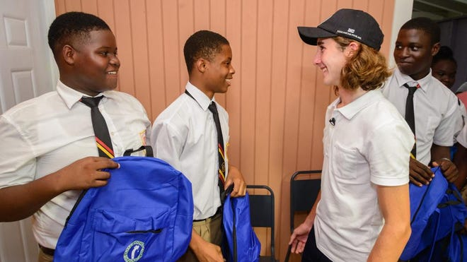 Rafe Cochran provides Iona High School students with backpacks during a dedication ceremony of two new buildings he helped construct with Food for the Poor in Tower Isle, St. Mary, Jamaica. Rafe raised money for the new classrooms during his annual golf tournament in April.