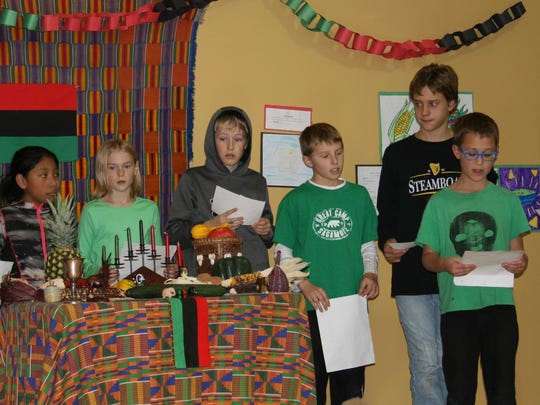 Fourth- and fifth-graders at The Schoolhouse share information about the symbols of Kwanzaa.