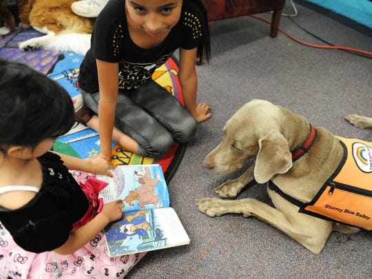 From right, Stormy Blue Bailey, a Weimaraner, listens as Isabella Virgen, 10, and Penelope, 3, read 101 Dalmatians at the Steinbeck Public Library in Salinas.