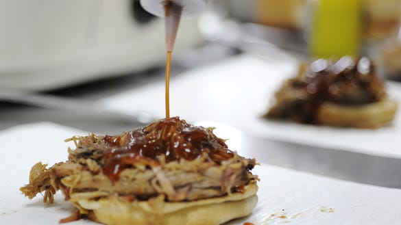 Homemade barbecue sauce is added to a brisket sandwich at Johnson's Boucaniere in this Advertiser file photo. Johnson's is one of many restaurants participating in Dine for the Diner this year.