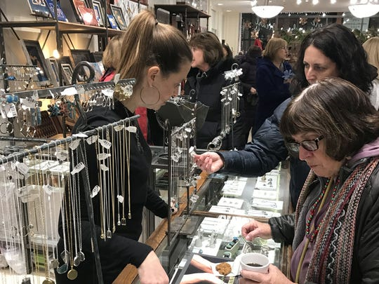 Shoppers examine the jewelry selections at The Artisan's