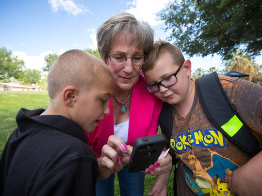 """U.S. Congressional candidate Merrie Lee Soules learns how to play augmented reality mobile game """"Pokémon Go"""" from 9-year-old Landenn Eaton, left and 10-year old Seth Justice at Young Park, Wednesday, July 27, 2016."""