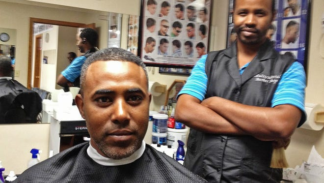 Berekat Haile with his barber, Chani Liben, at A Multicultural Barber Shop in Sioux Falls.