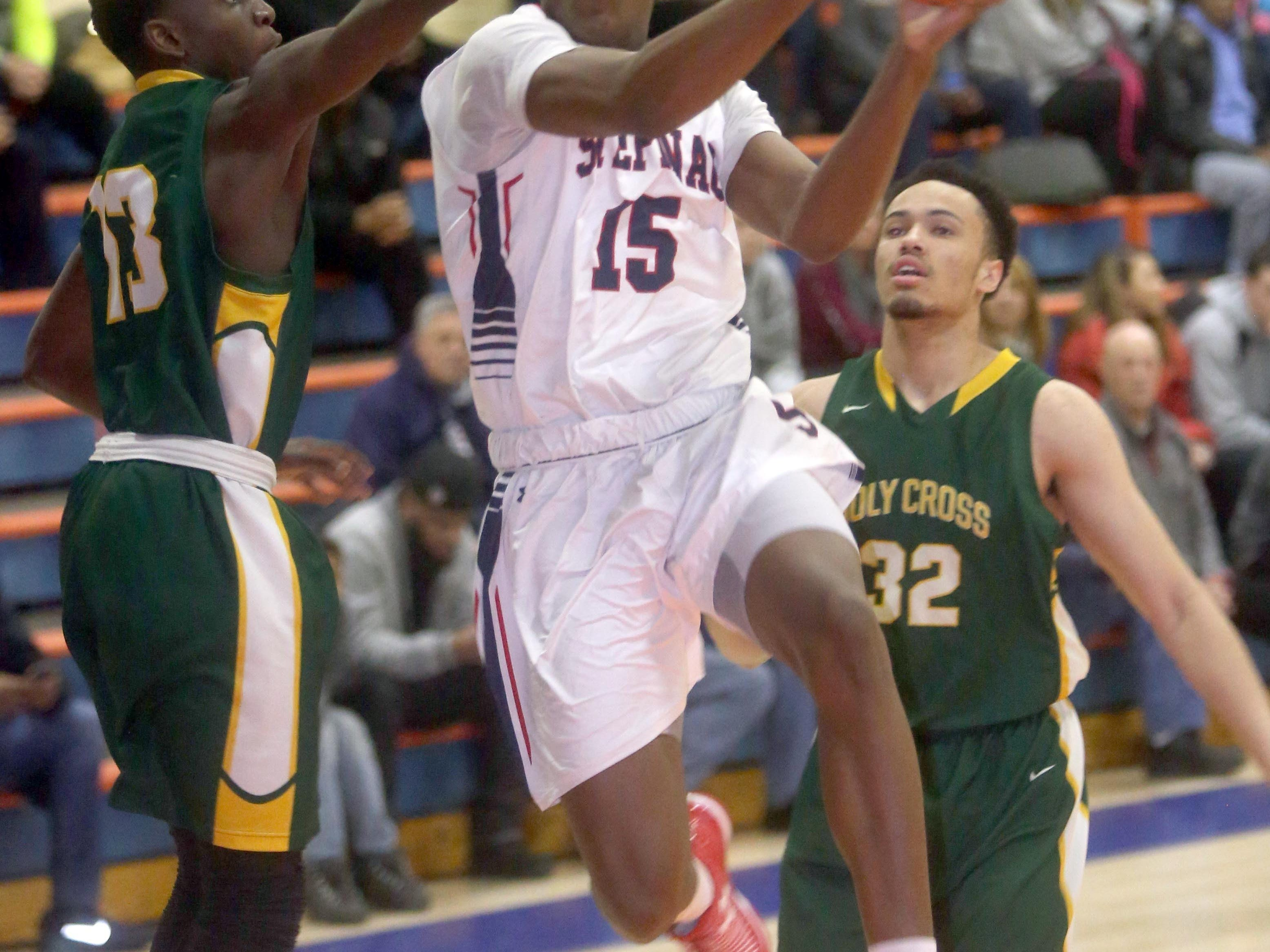 Stepinac's Aundre Hyatt splits Holy Cross defenders during a CHSAA second-round AA playoff game at St. Raymond High.