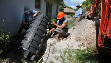 Stuart Public Works Department workers (from left) Johnathon Molina and Joel Zelaya install a grinder tank sewage system along with team leader Corky Kossen (background) in the backyard of a home on North Riverpoint Road in Stuart on Aug. 22, 2014. The grinder tank is a low pressure sewer pump system that replaces a septic system.
