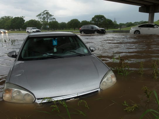 Motorists slowly drive past a flooded car on Interstate