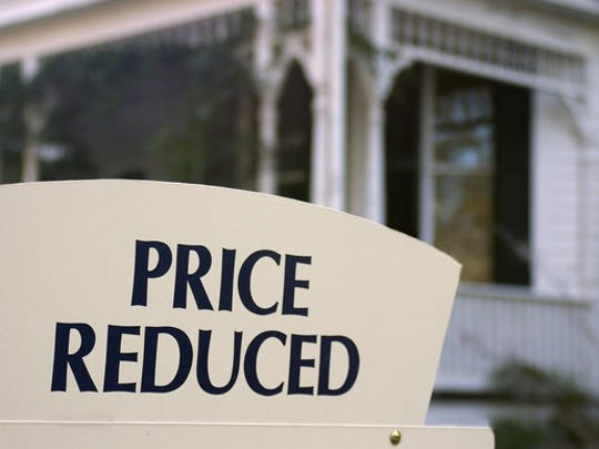 Home For Sale Price Reduced Sign Getty