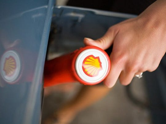 A person pumping Royal Dutch Shell gas.