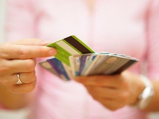 Woman choosing between handful of credit or debit cards.