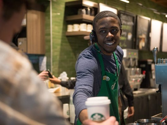 A Starbucks barista serving coffee.