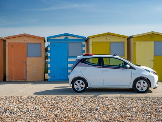 A white Toyota Aygo x-claim exterior pictured in front of colorful sheds on a beach