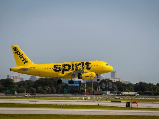 Exterior of landing Spirit A319 in bright yellow livery.