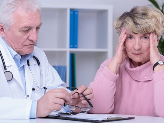 A frustrated senior woman clasping her head while her doctor presents her with a medical bill.