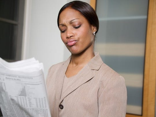 A woman closely examining data in a financial newspaper.