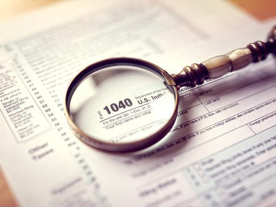 Tax return with a magnifying glass on top of it.