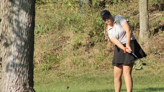 Kewanee's Mya Mirocha tries for a chip shot stuck between two trees on Friday at Spring Creek in Spring Valley.