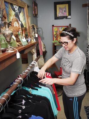 Tyler Walker, owner of Gracy Lu's in downtown Monmouth, rearranges some of her new inventory of clothes at the three-month-old business.