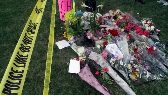 Flowers left by mourners pile up near the police tape