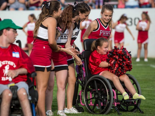 Haley Clark, 9, smiles and shakes her pom-poms after being introduced during Victory Day Friday, August 12, 2016 at Port Huron High School's Memorial Stadium.