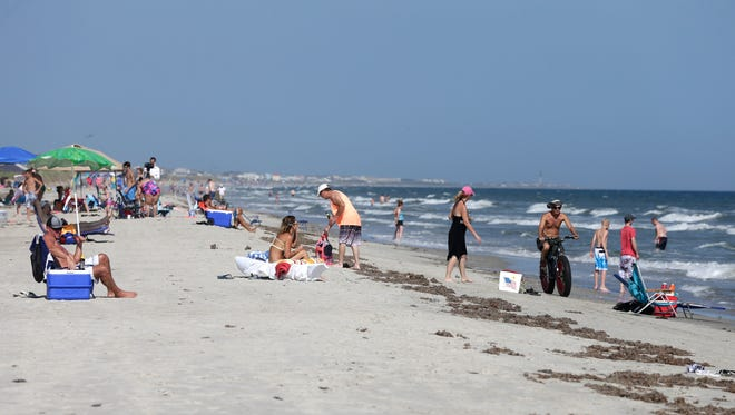 Vacationers relax on the bench and in the surf in Oak Island, N.C., Monday, June 15, 2015. A 12-year-old girl from Asheboro lost part of her arm and suffered a leg injury, and a 16-year-old boy from Colorado lost his left arm about an hour later and 2 miles away in two separate shark attacks late Sunday afternoon.