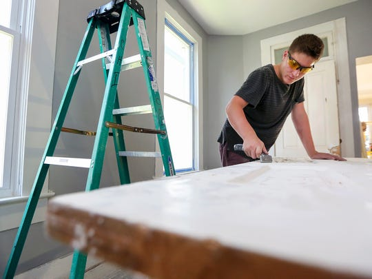 In this Sept. 20, 2016 photo, Four Oaks student Nick Herber, 16, scrapes paint from a door as part of the Housing Education and Rehabilitation Training program in Dubuque.