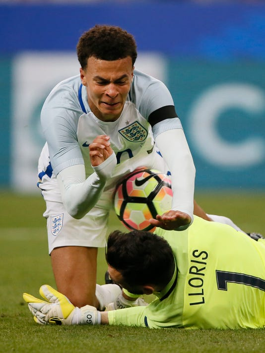 England's Dele Alli, top, falls over France goalkeeper Hugo Lloris during a friendly soccer match between France and England at the Stade de France in Saint Denis, north of Paris, France, Tuesday, June 13, 2017. (AP Photo/Francois Mori)