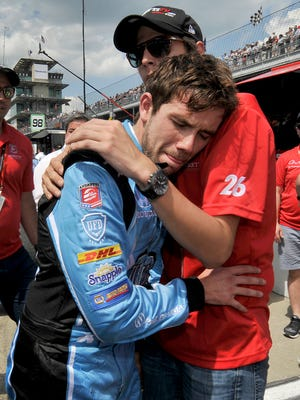 A dejected Carlos Munoz is consoled by a team member following his second-place finish in the 100th running of the Indianapolis 500 Sunday.