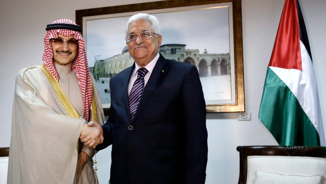 Palestinian President Mahmoud Abbas, right, shakes hands with Saudi Prince Alwaleed bin Talal, during their meeting in the West Bank city of Ramallah, Tuesday.