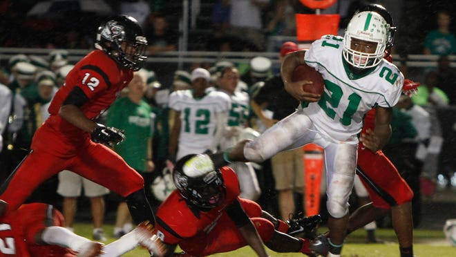 South Fort Myers defender Andre Polk, left, goes after Fort Myers ball carrier Terrance Moore Friday during first half play.
