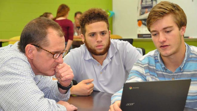 Robert W. Baird Senior Vice President Tim Duchow (from left) works with Shaun Hughes and Ryan Hayes on an investment plan that Hughes and Hayes have been working on in their Oconomowoc High School personal finance class.