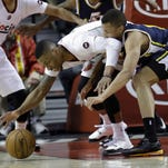 Utah Jazz guard Dante Exum, right, is hit in the face by Portland Trail Blazers guard Damian Lillard's elbow as they chase down a loose ball during the first half of an NBA basketball game  in Portland, Ore., Saturday, April 11, 2015. Lillard was called for a foul on the play.