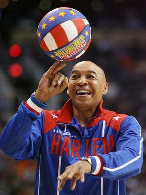"The Harlem Globetrotters' Fred ""Curly"" Neal performs during a timeout in the second quarter in an NBA game between the Indiana Pacers and the Phoenix Suns in Phoenix. Neal, the dribbling wizard who entertained millions with the Harlem Globetrotters for parts of three decades, has died the Globetrotters announced Thursday, March 26, 2020. He was 77. Neal played for the Globetrotters from 1963-85, appearing in more than 6,000 games in 97 countries for the exhibition team known for its combination of comedy and athleticism."