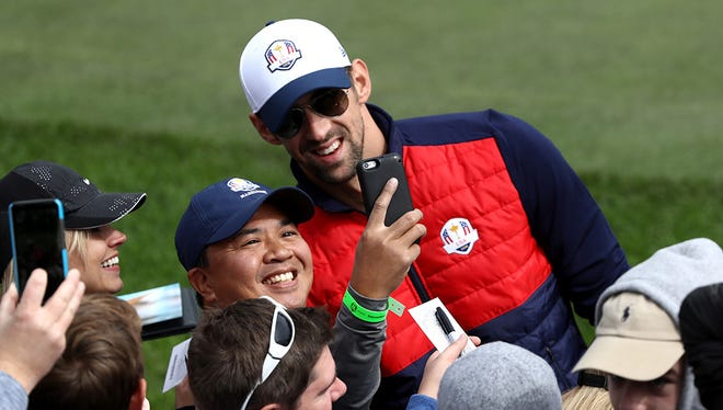 Swimmer Michael Phelps  takes a selfie with a fan during the 2016 Ryder Cup Celebrity Matches at Hazeltine National Golf Club on September 27, 2016 in Chaska, Minnesota.