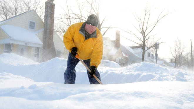 Jason Struthers, tries to shovel out his driveway Monday, Feb 2, in Port Huron.