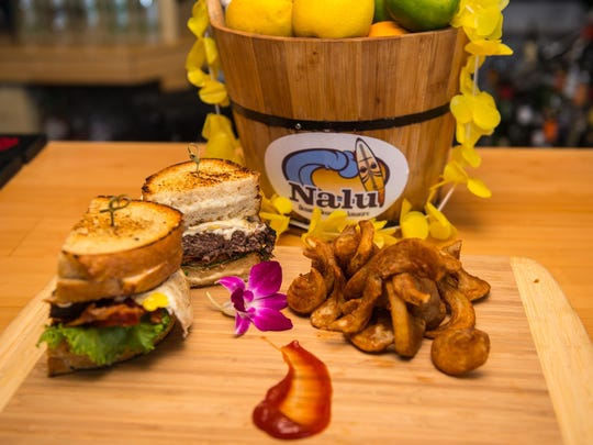 The Ono Burger from Nalu Surf Bar is topped with American cheese, two fried eggs, bacon, lettuce, tomato and mayo — all between two grilled cheese sandwiches.