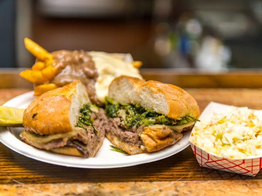 Murphs Beef and Ale's Roast Beef Supreme, topped with broccoli rabe with gravy and cheese fries and a side of coleslaw.