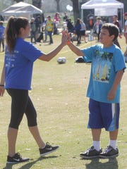Alexi Mejia, a volunteer gives encouragement on a soccer drill at the Palm Desert Civic Center as part of DisAbility Sports Festival.