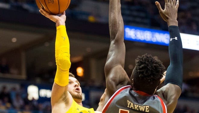 Marquette guard Andrew Rowsey puts up a shot against St John's forward Kassoum Yakwe on Tuesday.