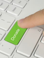 Finger pushing green donate button