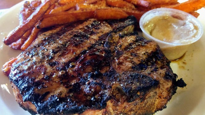 The most popular item at Morrie's Place is its thick, grilled pork chop, seen here with sweet potato fries.