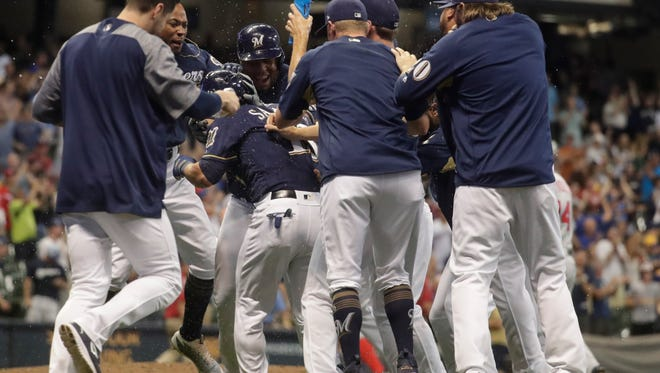 Tyler Saladino (middle) is mobbed by his Brewers teammates after he drove in the winning run against the Nationals with a sacrifice fly in the 10th inning on Tuesday night.