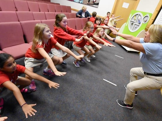 Mary Smith, a health educator at the Byrnes Health Education Center, does a cardio exercise with York Country Day students during a nutrition session at Children's Wellness Days. The event, organized by the York Hospital Auxiliary and the Byrnes center, introduces students to a number of health topics including nutrition, cyber safety, and bullying.