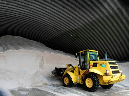 At the TDOT Region 3 complex a worker scoops salt from